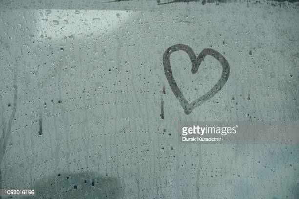 a heart painted on a misted window.heart on misted glass. - steam stock pictures, royalty-free photos & images