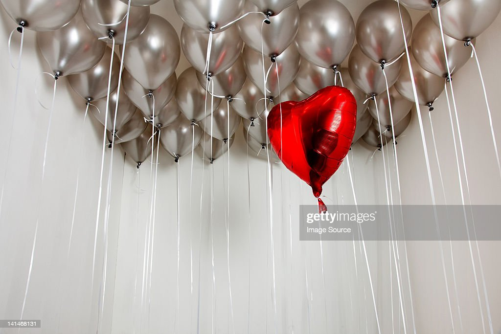 Heart shape balloon amongst plain balloons : Stock Photo