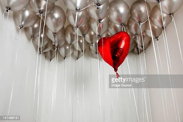 Heart shape balloon amongst plain balloons