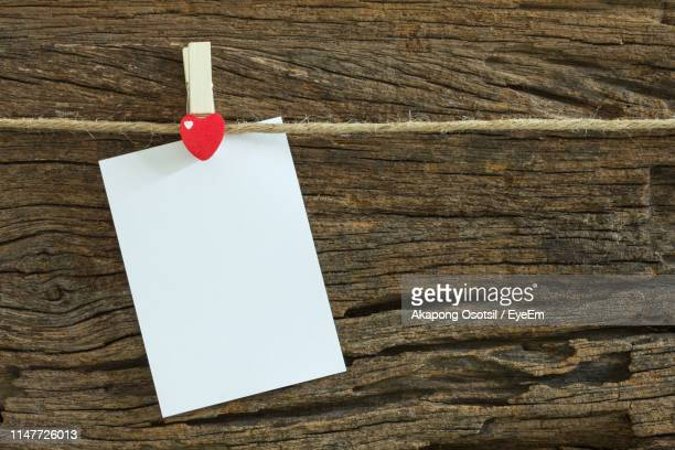 heart shape binder clip with blank paper hanging on rope against wood - binder clip stock pictures, royalty-free photos & images