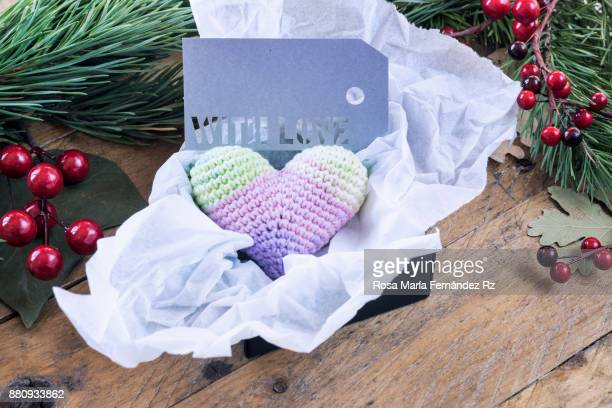 Heart shape crochet and greeting card with the word 'with love' written into gift box framed with fir tree branches,  leaves and mistletoe seed on wooden background. Selective focus and copy space.