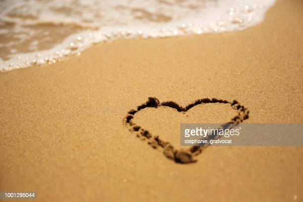 Heart shape drawing in the sand on a beach
