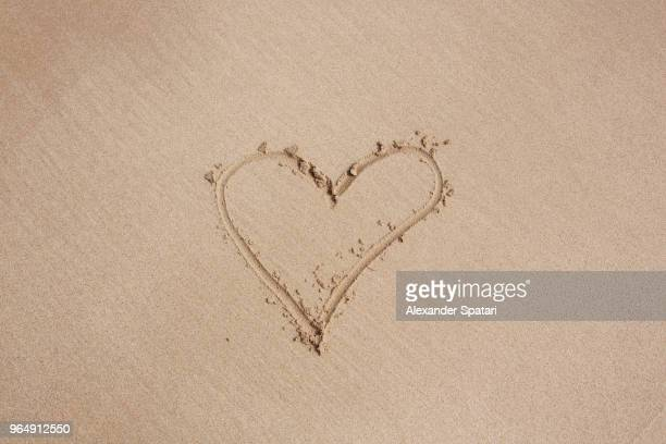 heart shape drawing made with finger on a sand of the beach - heart background stock pictures, royalty-free photos & images