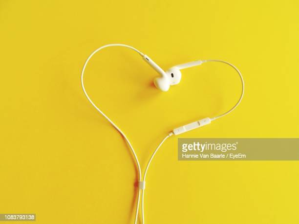 Heart Shape Formed Of Headphones Over Yellow Background