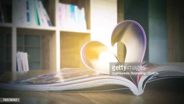 Heart Shape Forming On Book Over Table
