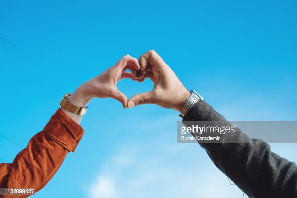 heart shape from couple hands - ハネムーン ストックフォトと画像