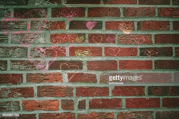 Heart shape graffiti drawn on brick wall