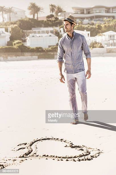 Heart shape in sand and young man strolling on beach, Cape Town, South Africa