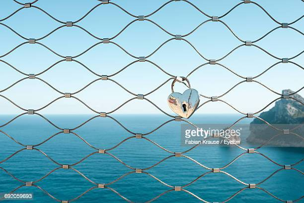 Heart Shape Love Lock Hanging On Fence Against Mediterranean Sea