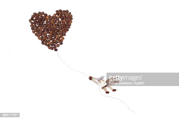 Heart Shape Made Of Coffee Beans Over White Background