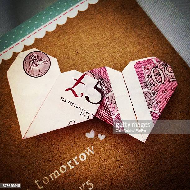 heart shape made of papers on table - british pound sterling note stock pictures, royalty-free photos & images