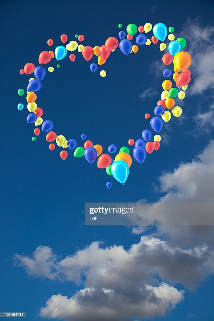 Heart shape of balloons against sky with puffy clouds : Stockfoto