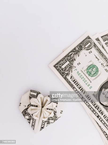 Heart Shape Of Paper Currency Against White Background