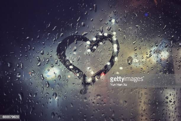 heart shape on glass at rainy night - romantic rainy day stock photos and pictures