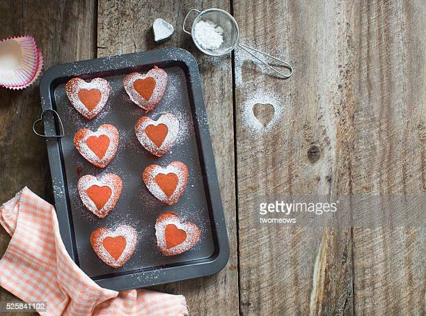 Heart shape pink strawberry cupcake fresh from oven on rustic wooden kitchen table top. Text space image.