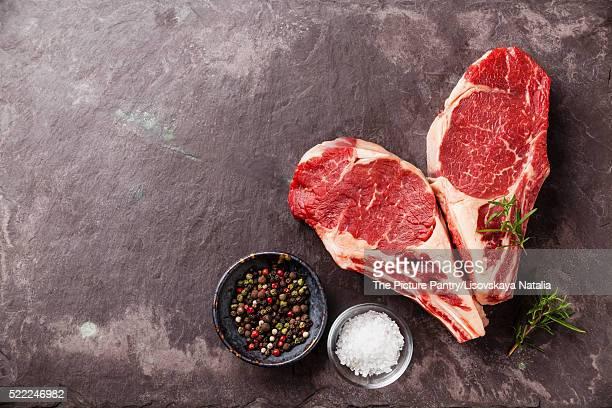 Heart shape Raw fresh meat Ribeye Steak with rosemary, pepper an