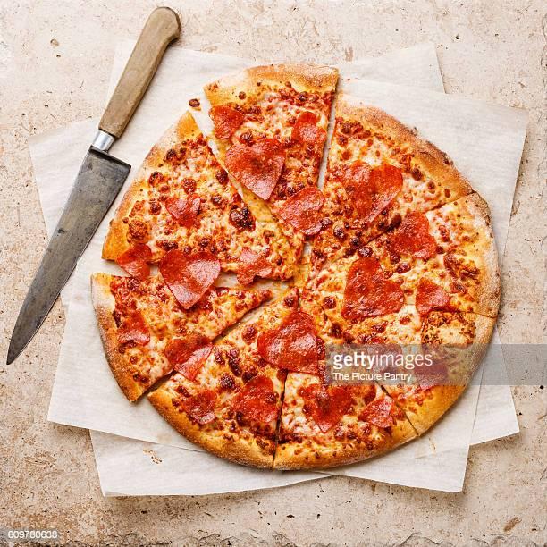 Heart shape sliced Pepperoni Pizza on stone travertine background