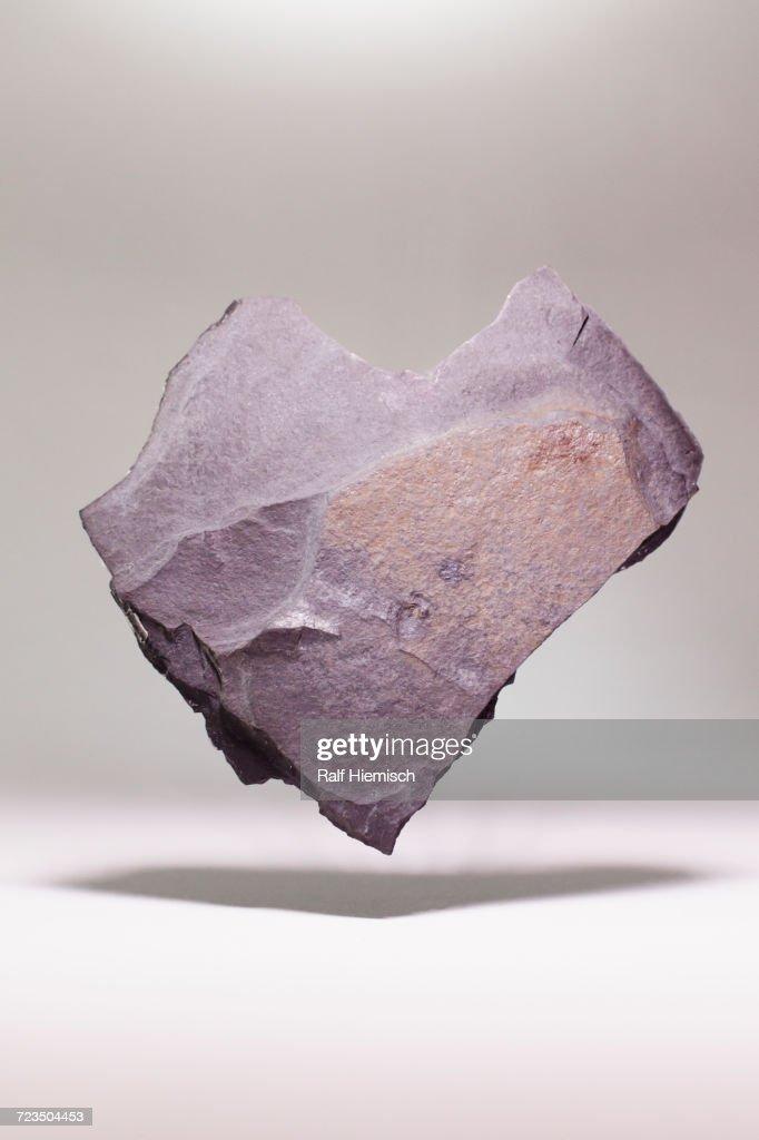 Heart shape stone levitating over white background : Stock-Foto