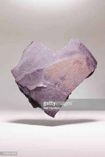 heart shape stone levitating over white background - pietra roccia foto e immagini stock