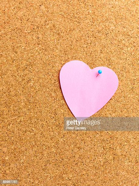 Heart shaped adhesive note on notice board.
