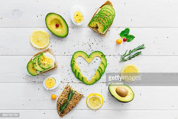 Heart shaped avocado slices with Avocado, egg, bread and lemon
