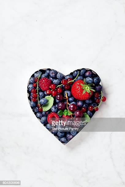 Heart shaped berries on white marble background. Flat lay