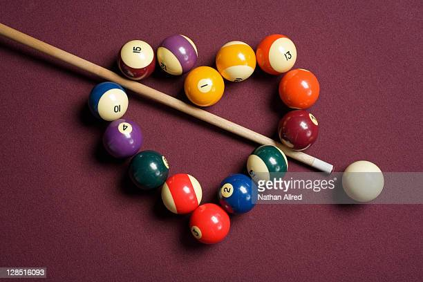 Heart shaped billiard balls with cue ball and stick