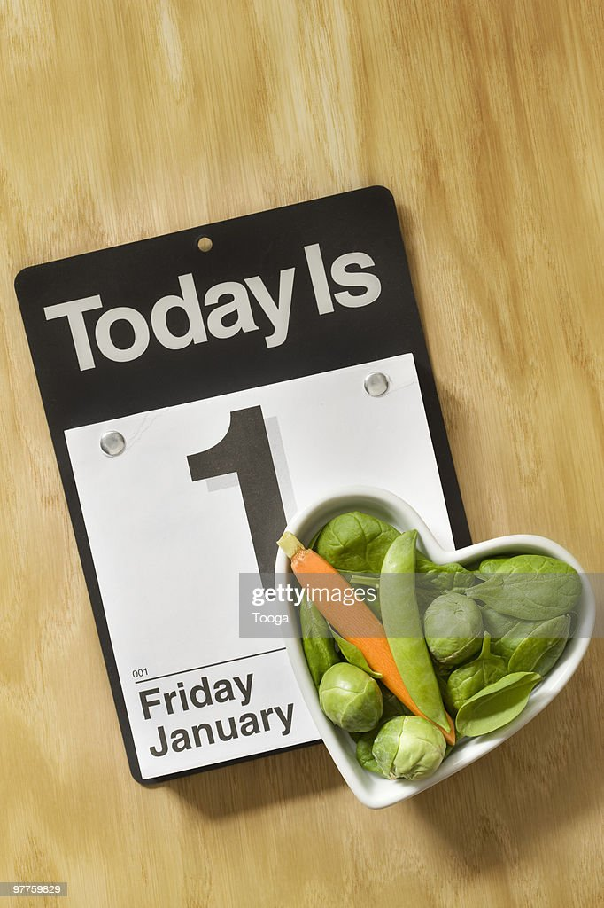 Heart shaped bowl of veggies and calender  : Stock Photo