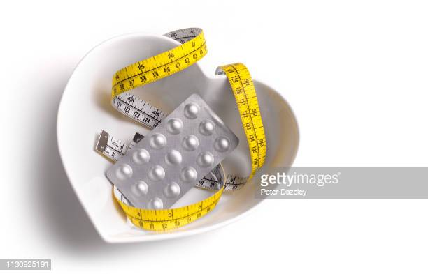 heart shaped bowl with slimming pills - malnutrition stock pictures, royalty-free photos & images