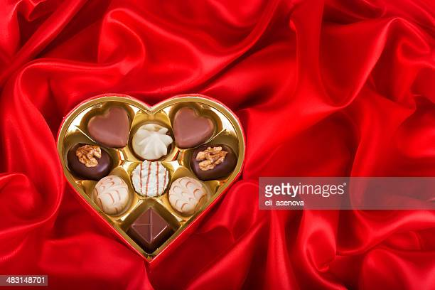 Heart Shaped Box of Candy on red satin background