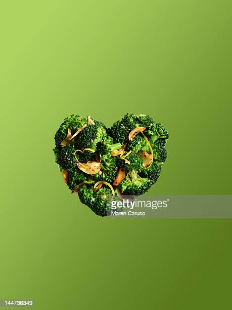 Heart shaped broccoli on green background