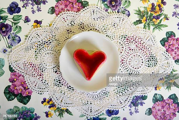 a heart shaped cake on a plate - doily stock photos and pictures