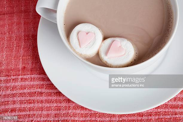 Heart shaped candies in cappuccino (close-up, directly above)