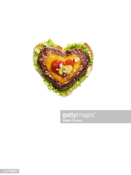 Heart shaped cheese burger on white background