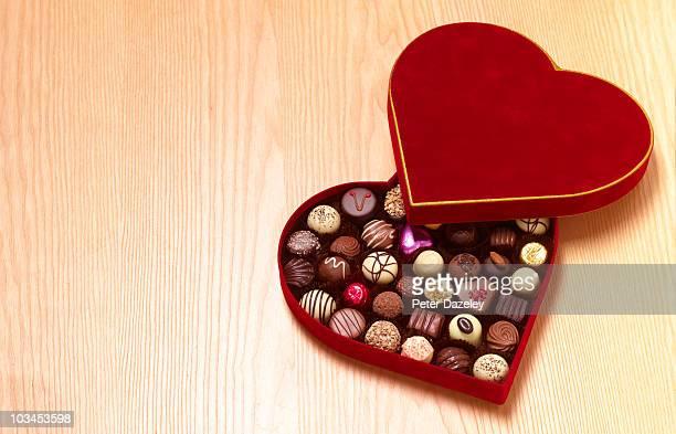 Heart shaped chocolates on wood background
