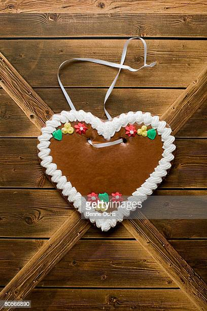 A heart shaped cookie hanging on a wooden wall