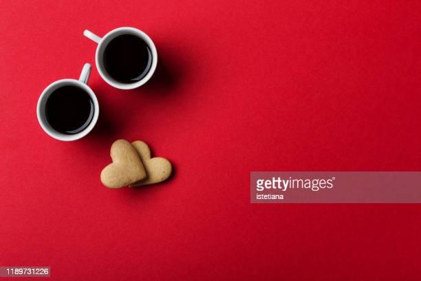 heart shaped cookies and coffee cups on red  background - twee objecten stockfoto's en -beelden