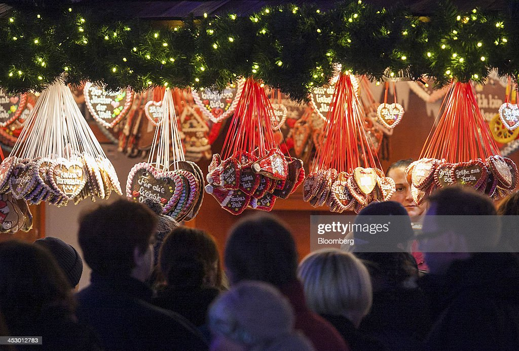 Heart shaped cookies hang on display as shoppers gather by a stall at Alexanderplatz Christmas market in Berlin, Germany, on Saturday, Nov. 30, 2013. Euro-area economic growth slowed to 0.1 percent in the third quarter after a 0.3 percent gain in the previous three months. Photographer: Krisztian Bocsi/Bloomberg via Getty Images