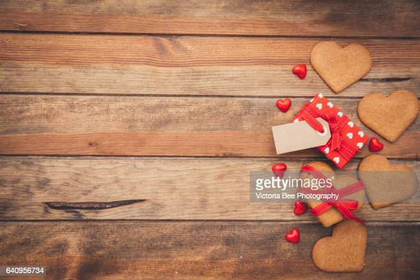 Heart shaped cookies with gift on wooden background
