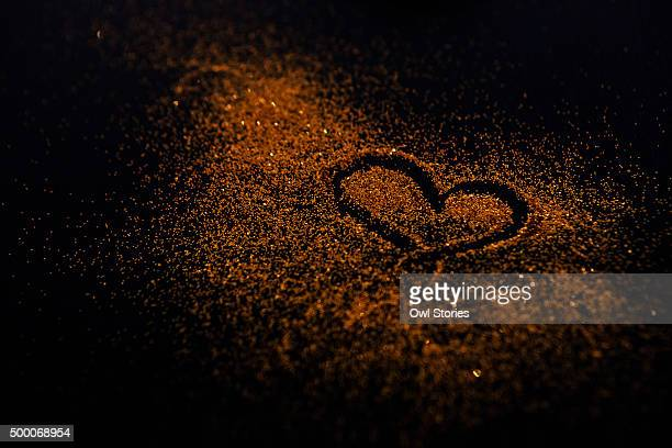 Heart shaped doodle drawn in golden colored glitter