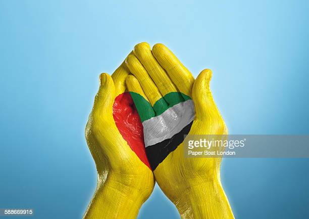 UAE heart shaped flag painted on a hand