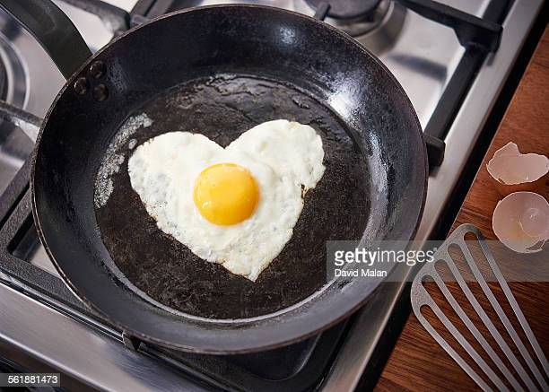 Heart shaped fried egg in a pan