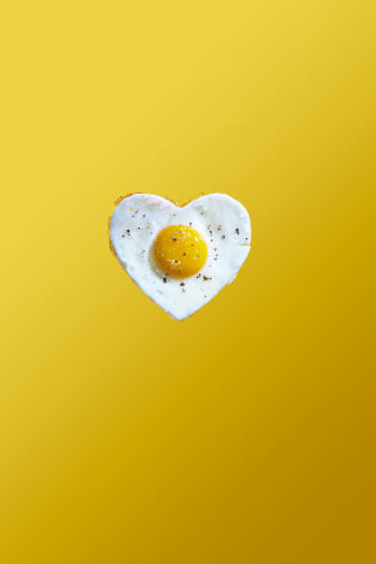 Heart shaped fried egg on yellow background - gettyimageskorea