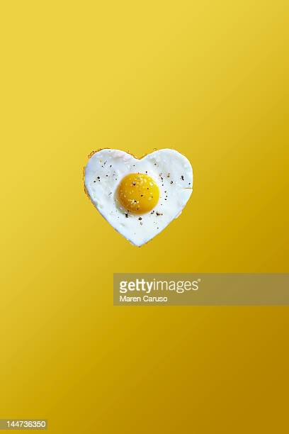 heart shaped fried egg on yellow background - fried eggs stock pictures, royalty-free photos & images