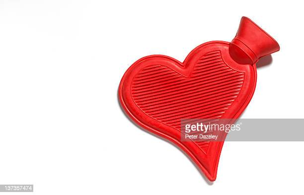 Heart shaped hot water bottle on white background