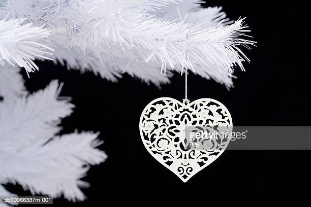 Heart shaped ornament hanging on Christmas tree, close-up