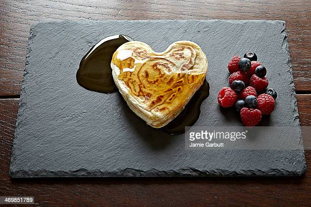 Heart shaped pancakes smothered in syrup