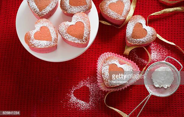 Heart shaped pink strawberry cupcakes and party bottle drinks on red table top background. Overhead view.