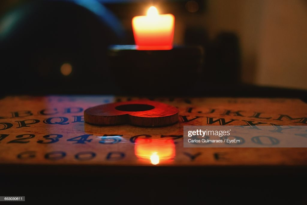 Heart Shaped Planchette On Ouija Board By Candle In Darkroom : Stock Photo