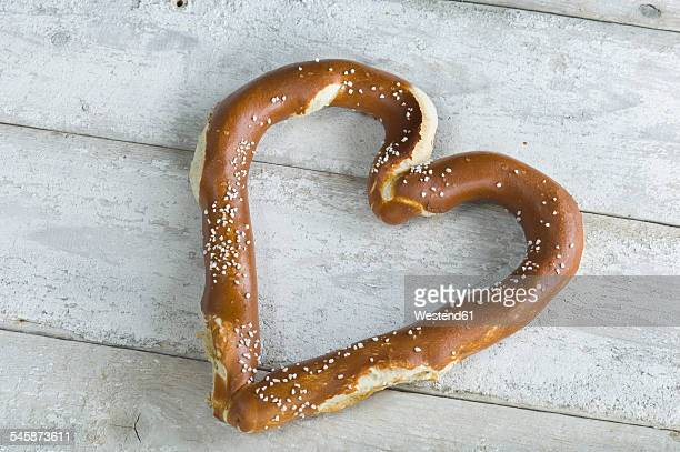 Heart shaped pretzel on white wood
